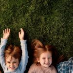 Top view of smiling parents, little girl and boy having fun while lying on a grass. Children, family and nature concept. Horizontal shot