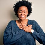 Young beautiful African American afro woman with curly hair wearing casual sweater smiling with hands on chest with closed eyes and grateful gesture on face. Health concept.
